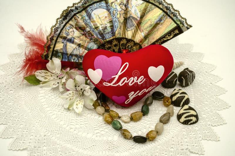 La vie avec un coeur rouge et une inscription toujours vous aiment, perles, une fan, les chocolats, fleurs sur une serviette blan images stock