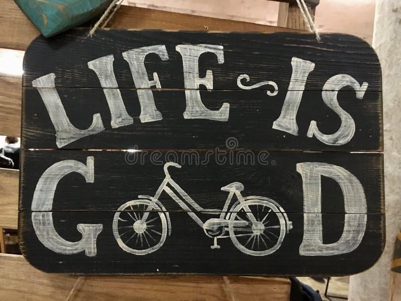 La vie blanche d'inscription est bonne sur un vieux conseil noir en bois avec une bicyclette photo stock