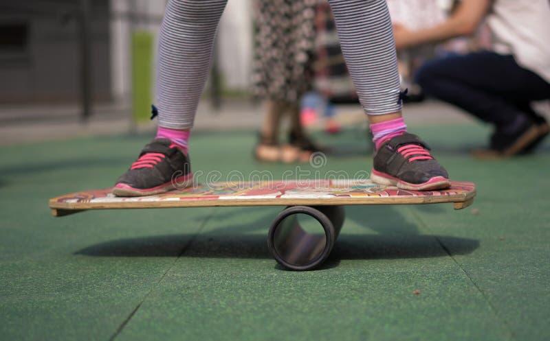 La vie dans une ville moderne - une fille monte un équilibre-conseil sur un terrain de jeu avancé photos stock