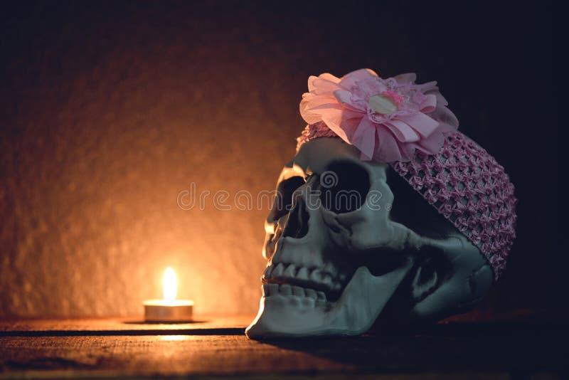 La vie de distillateur de crâne - crâne humain avec le bandeau rose autour décoré à la partie de Halloween et à la bougie légère  photo stock