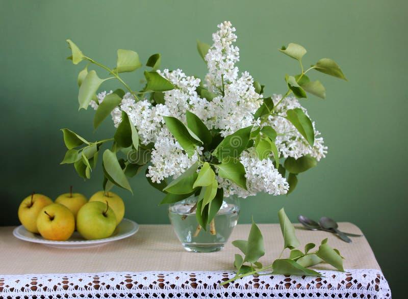 La vie de distillateur de ressort avec un bouquet des lilas et des pommes blancs image libre de droits