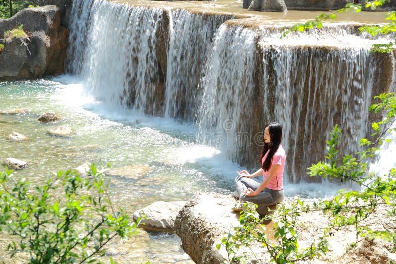 La vie heureuse paisible, la femme chinoise asiatique négligente font le yoga avant cascade photo libre de droits