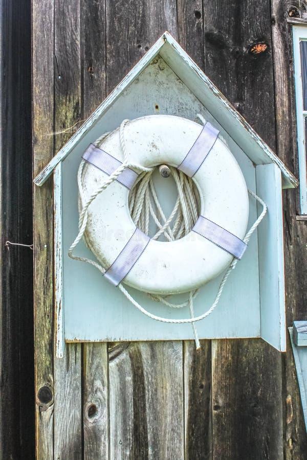 La vie que vous sauvez - un dispositif flottant de sauvetage, sale et grincheux, est accroché dans un petit porte-maison en bois  photo stock