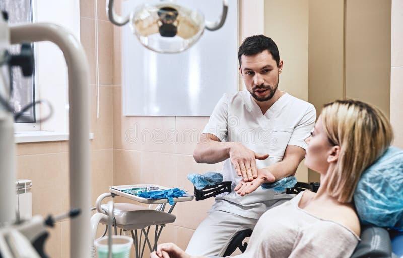 La vie s'ouvrent avec un sourire plus blanc Le dentiste explique en détail le progrès du traitement dentaire patient dans moderne photos libres de droits