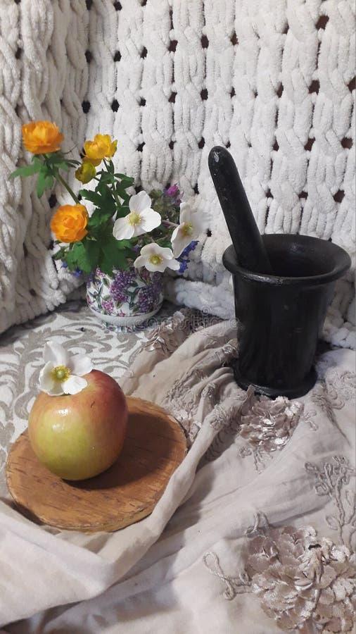 La vie toujours avec Apple, les fleurs oranges et le mortier noir image stock