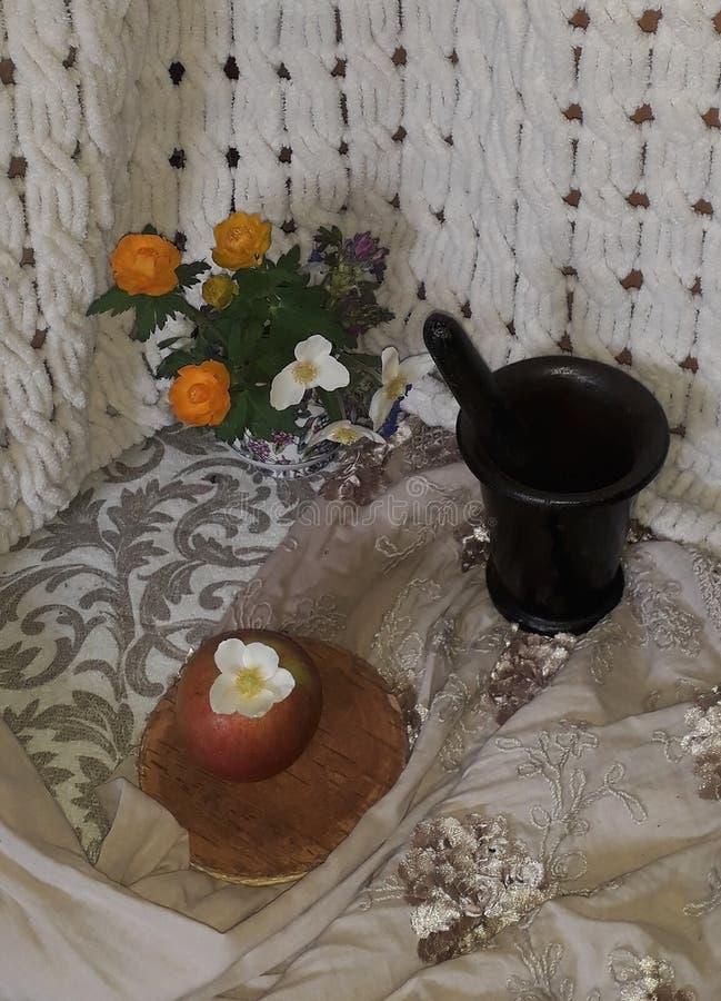 La vie toujours avec Apple, les fleurs oranges et le mortier noir image libre de droits