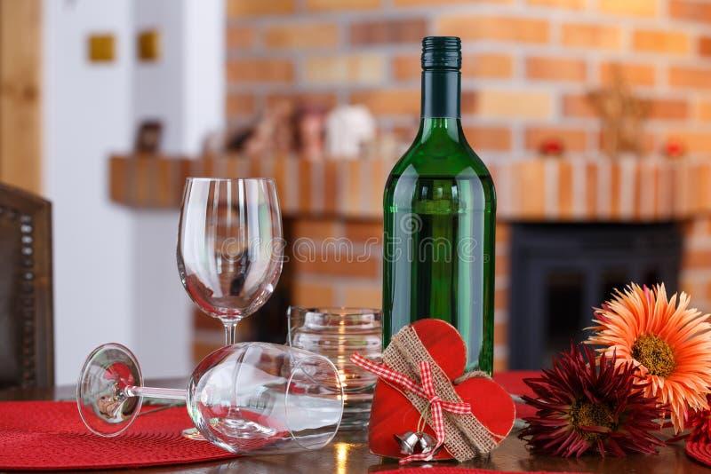 La vie toujours avec des bouteilles de vin, des verres, des fleurs et le symbole de coeur, photographie stock libre de droits
