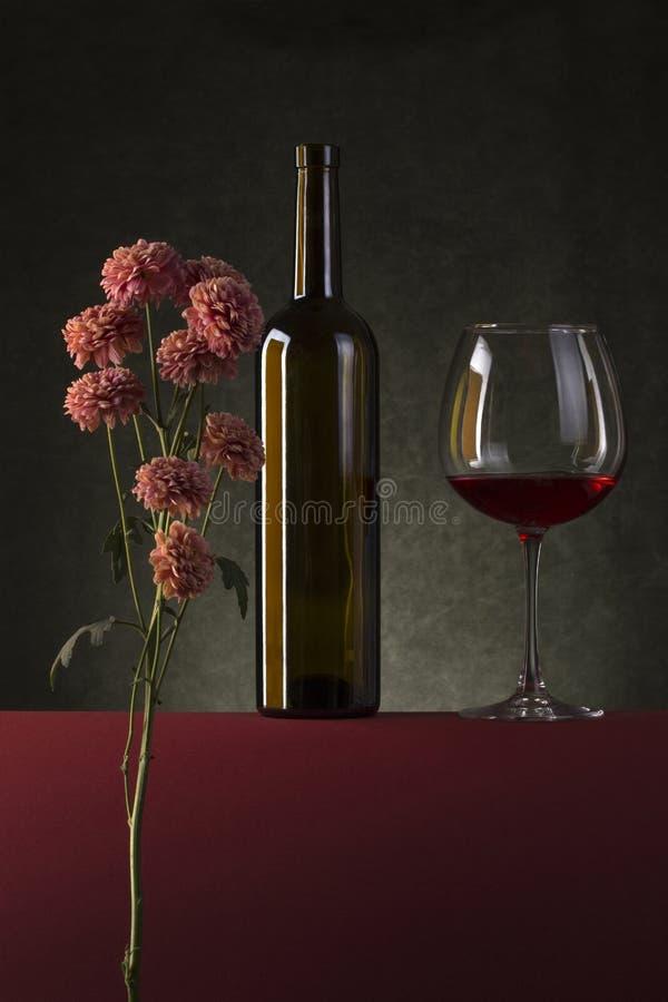 La vie toujours avec des fleurs, une bouteille et un verre de vin photos libres de droits
