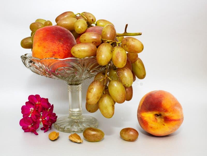 La vie toujours avec des pêches et des raisins de fruit sur un vase en verre sur un fond gris ou argenté image stock