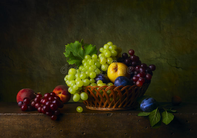 La vie toujours avec des poires, des raisins et des prunes photos stock