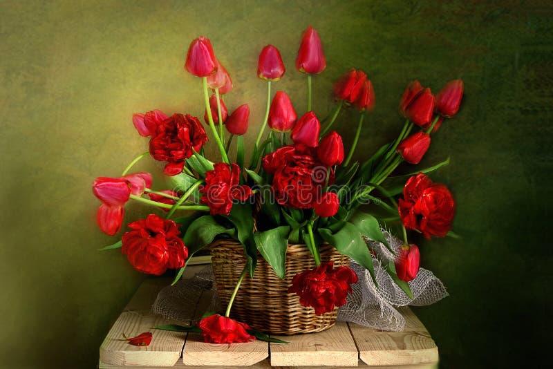 La vie toujours avec le bouquet des jonquilles de ressort, tulipes dans un panier photo stock