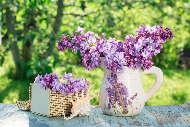 La vie toujours avec le lilas dans une cruche, un cercueil, une coquille sur une table en bois photos stock