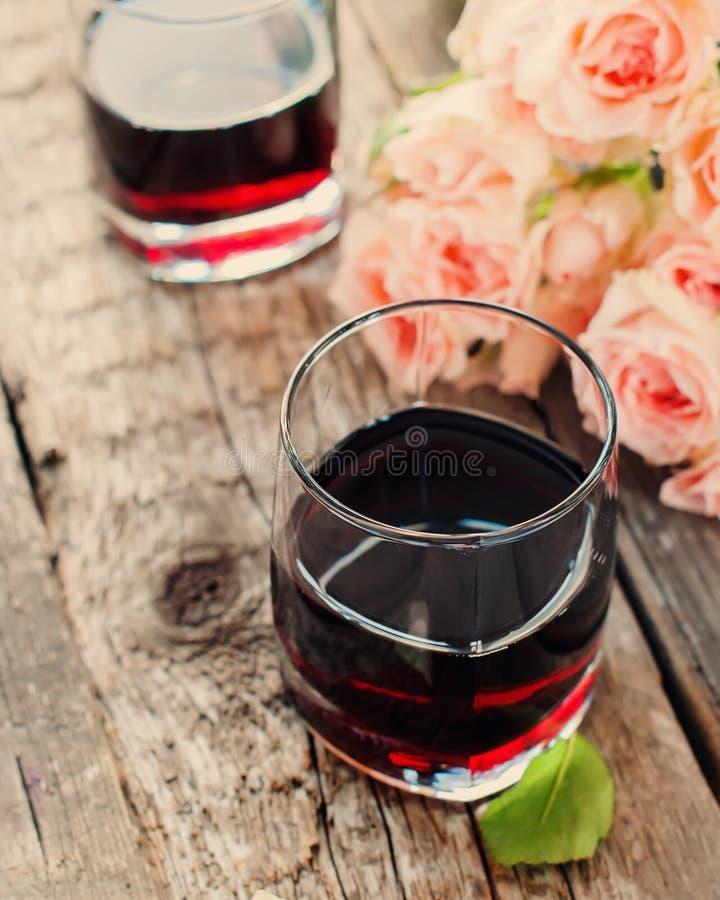 La vie toujours avec le vin rouge et le bouquet des roses, modifiés la tonalité image stock