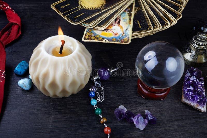 La vie toujours avec les cartes de tarot, les pierres magiques et les bougies sur la table en bois Fortune indiquant le seance ou photo libre de droits