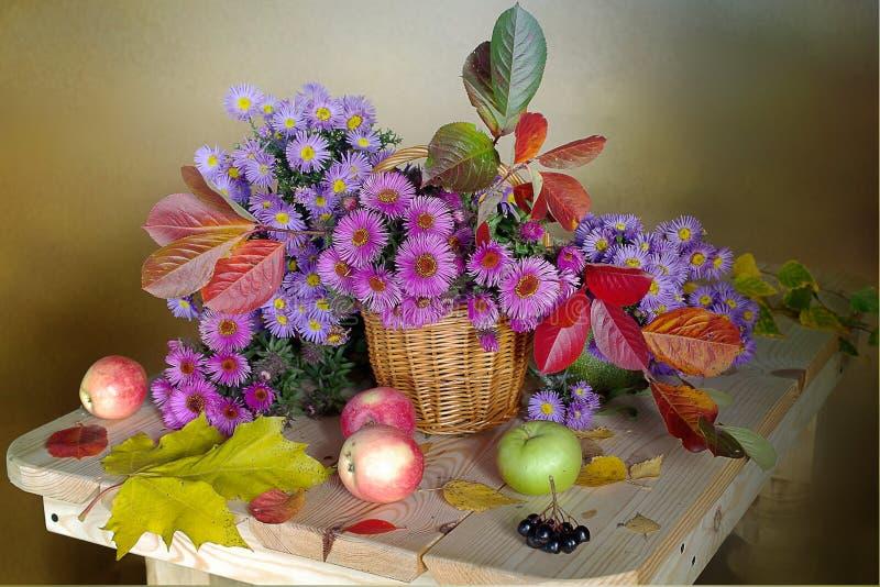 La vie toujours avec les feuilles d'automne et le rose de septembre, tons bleus dans un panier sur un fond brun photographie stock