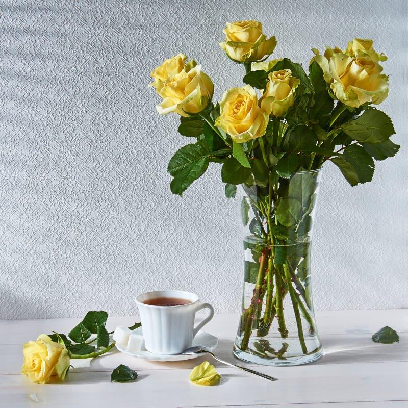 La vie toujours avec un bouquet des roses et d'une tasse de thé photographie stock