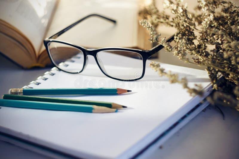 La vie toujours avec un livre, un carnet, des crayons et un bouquet des fleurs image stock