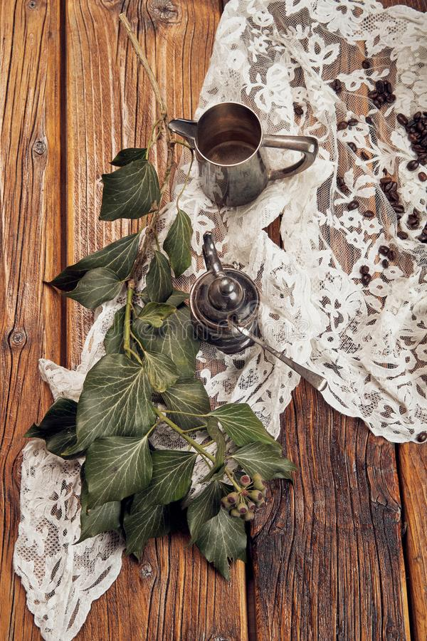 La vie toujours avec un petit pot de café en métal, une tasse de sucre en métal et le lierre sur une vieille table en bois images libres de droits