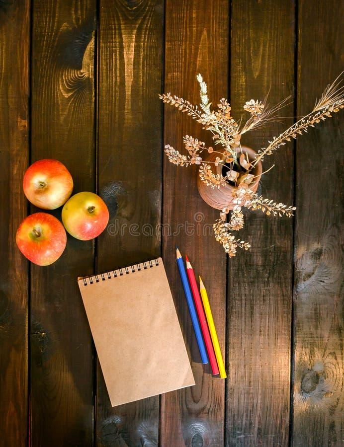 La vie toujours avec un vase, un bloc-notes et des pommes image stock