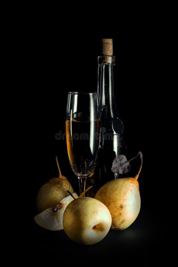 La vie toujours ; bouteille de vin, des poires entières et de la moitié sur un fond foncé images libres de droits