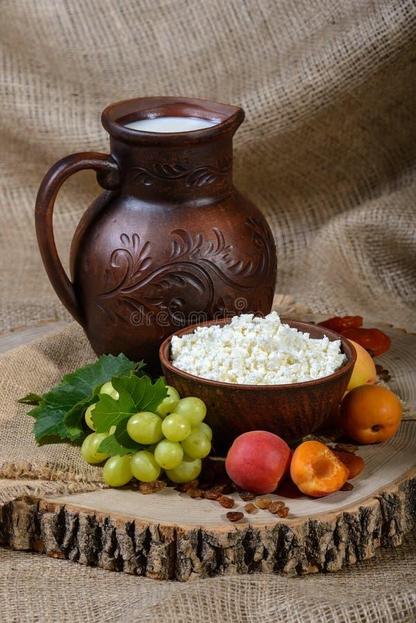 La vie toujours dans un style rustique : fromage blanc dans un plat, un lait et des fruits d'argile sur le fond en bois image libre de droits