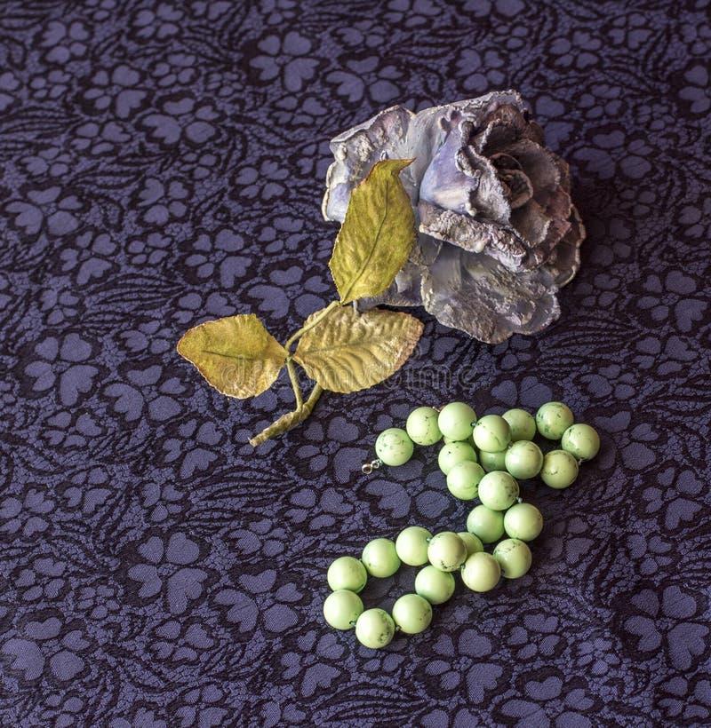 La vie toujours de la rose artificielle avec des perles de malachite sur le fond de textile image stock