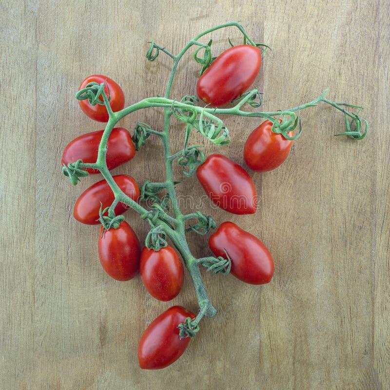 La vie toujours des branches mûres de tomates-cerises sur une table en bois brune photographie stock libre de droits