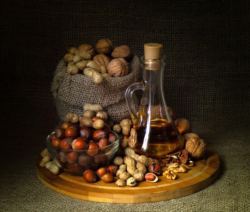 La vie toujours ; noix, arachides, noisettes, huile de noix, sur le conseil image libre de droits