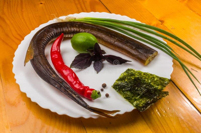 la vie toujours - orphie fumée avec la chaux, Basil, oignons verts, piment, puces de nori, épices, huile d'olive dans un plat en  photos stock