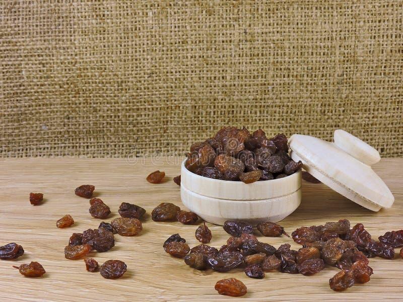 La vie toujours, raisin sec, cuvette en bois image libre de droits