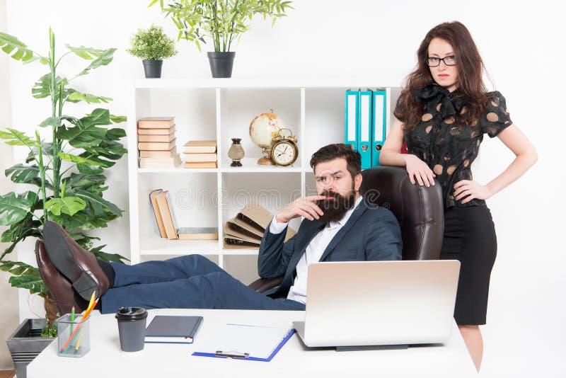 La vie typique de bureau Le patron barbu de hippie d'homme se reposent dans l'intérieur en cuir de bureau de fauteuil Patron et f images stock