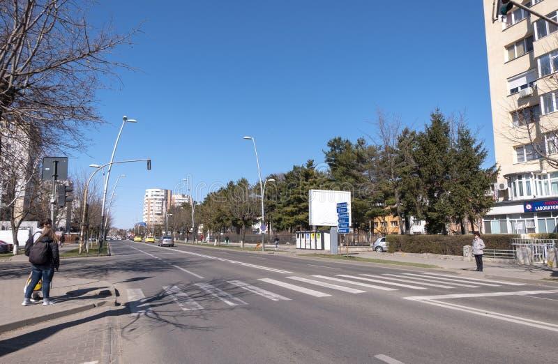 La vie urbaine dans Bacau, une ville en Roumanie du nord-est, avec des personnes attendant pour traverser la rue images libres de droits