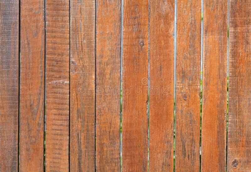La vieille barrière en bois grise superficielle par les agents est peinte avec une couleur orange lumineuse, plan rapproché image libre de droits