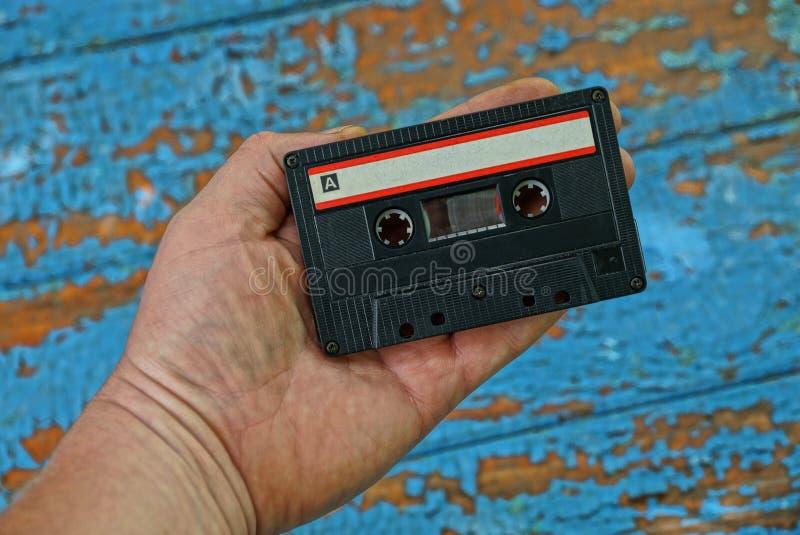 la vieille cassette sonore est sur une main sur un fond bleu photo stock