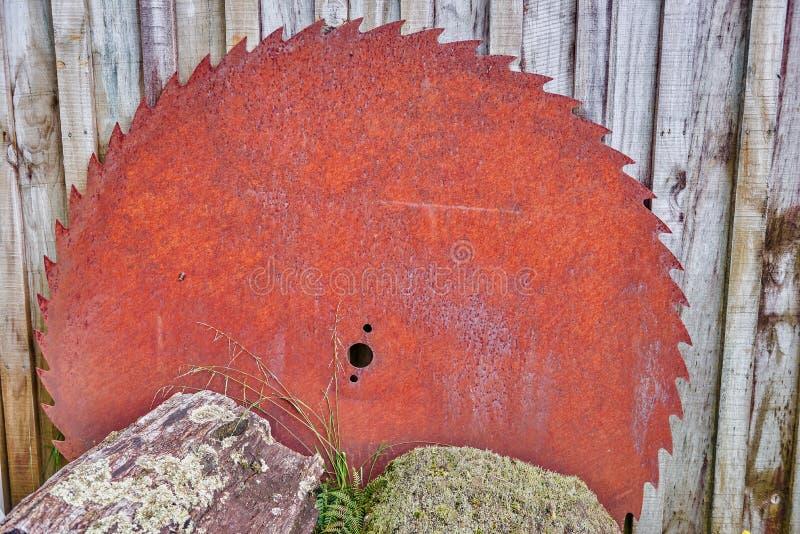 La vieille circulaire rouillée a vu le mensonge hors d'usage contre le côté d'une grange photos stock