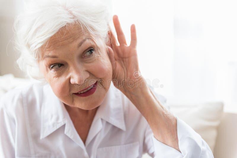 La vieille dame a la difficulté avec la perception auditive images libres de droits