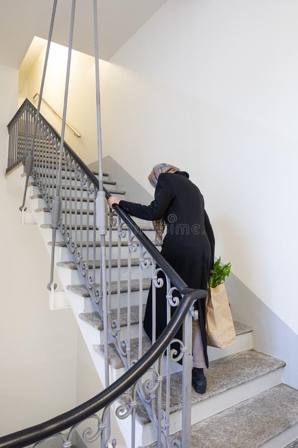 La vieille dame rentre à la maison après avoir fait les courses images stock