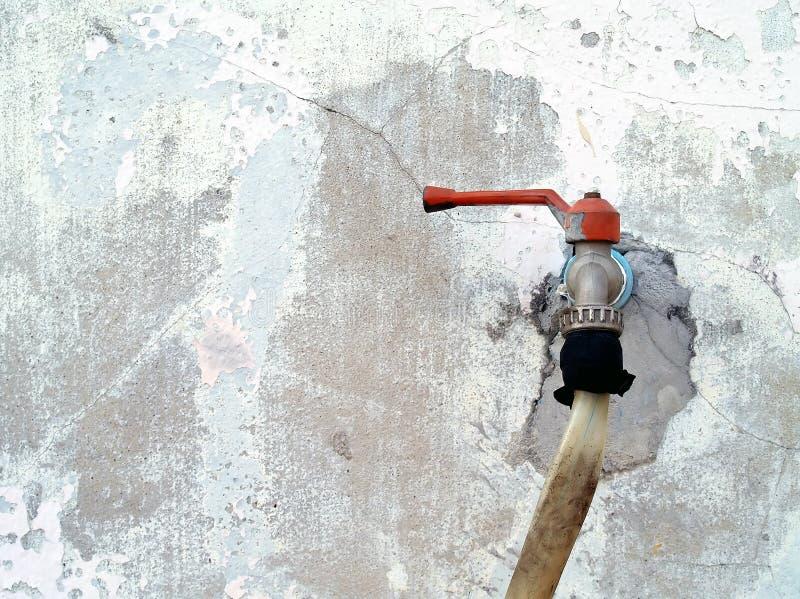 La vieille eau de robinet en métal avec le tube en caoutchouc sur le fond blanc cassé de mur en béton images libres de droits