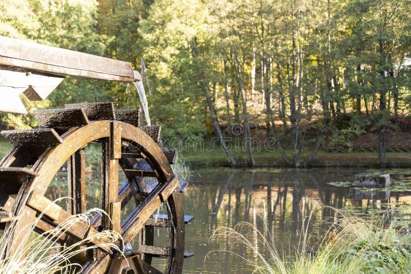La vieille eau mobile de moulin à eau de roue de vintage éclabousse dans l'étang photo stock