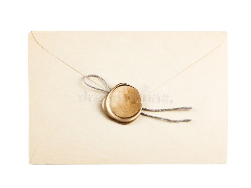 La vieille enveloppe de courrier avec le joint de cire d'or emboutit photo stock