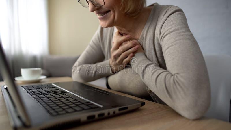 La vieille femelle a enchanté pour parler aux enfants dans l'Internet regardant l'écran d'ordinateur portable image stock