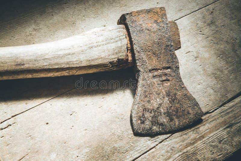 La vieille hache rouillée se trouve sur le plancher en bois rustique images stock