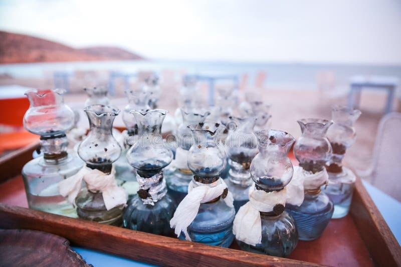 La vieille huile les lampes qu'en verre avec des difficultés de DIY ont recueilli sur le Tableau sur le Grec soit images libres de droits