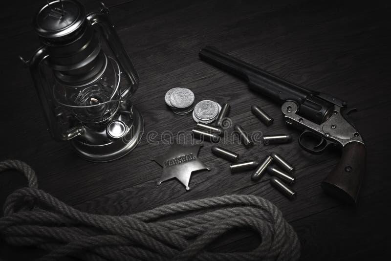 La vieille lanterne froide occidentale de souffle, rassemble l'insigne et le revolver avec des cartouches images stock