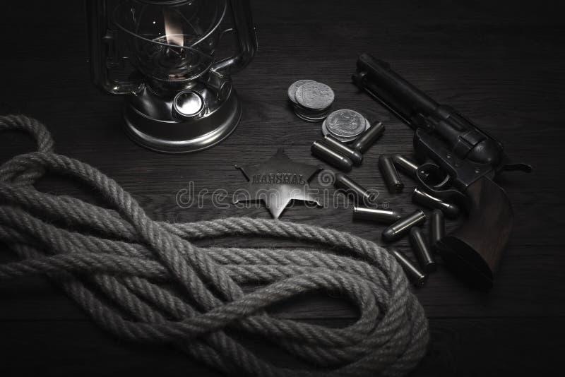 La vieille lanterne froide occidentale de souffle, rassemble l'insigne et le revolver avec des cartouches image libre de droits