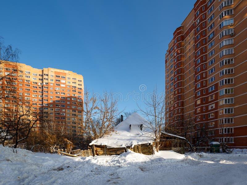 La vieille maison en bois délabrée devant les nouvelles maisons résidentielles Balashikha, Russie photos libres de droits