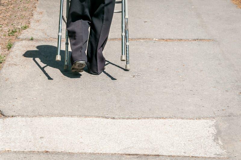 La vieille marche de femme handicapée seule et déprimée sur la rue dans la ville a aidé par le bâton ou la canne réglable de marc image stock