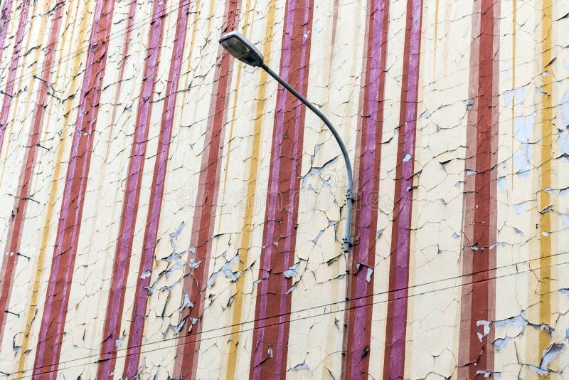 La vieille peinture de ?caillement de ?miettage sur un vieux et vieillissant mur de maison d'appartement avec le r?verb?re La pei photos libres de droits