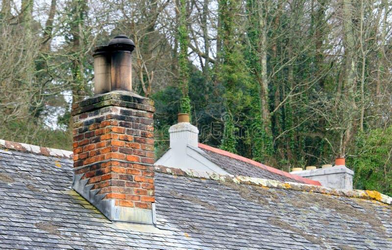 La vieille pile de cheminée de brique rouge sur une ardoise a couvert le bâtiment, d'ano photo libre de droits