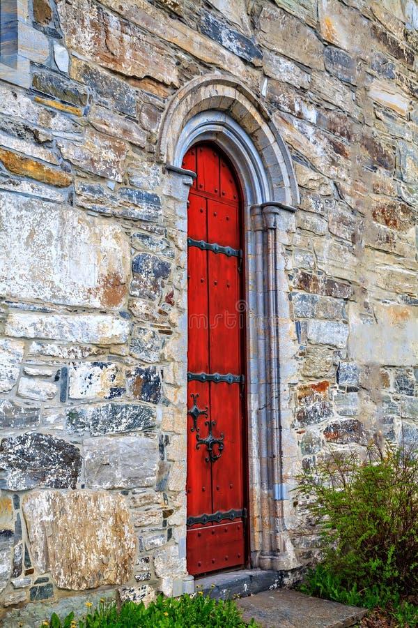 La vieille porte rouge au bâtiment en pierre photographie stock libre de droits